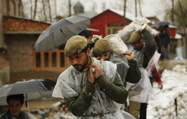 Jammu and Kashmir policemen carry sand bags to repair a breach in an embankment in a flooded area of Srinagar, Indian-controlled Kashmir, Wednesday, April 1, 2015. Although flood waters were receding, residents in the main city of Srinagar were bracing for more trouble as the meteorological office has predicted more rain over the next few days. (Photo by Mukhtar Khan/AP Photo)