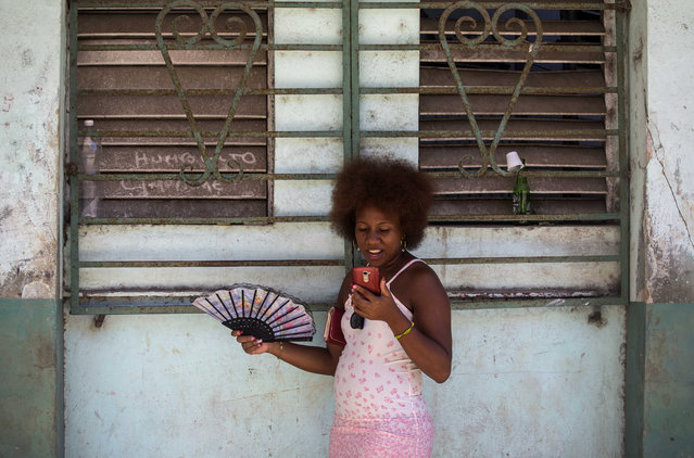 A woman uses her smartphone to surf the internet in Havana, Cuba, Wednesday, August 22, 2018. The state telecommunications company of Cuba launched on Wednesday the latest, and most extensive, of a recent series of test runs of a mobile network that would give ordinary citizens greater access to the internet than has existed before on the island. (Photo by Desmond Boylan/AP Photo)