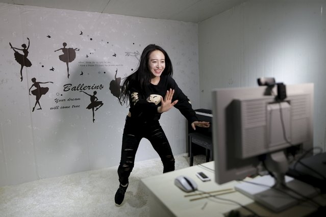 Online hostess Sun Xiaohou gestures to fans as she tries to adjust the web camera before her dance performance broadcast in Beijing April 1, 2015. (Photo by Jason Lee/Reuters)