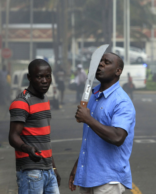 In this photo taken in  Durban, South Africa, on Tuesday, April 14, 2015, an immigrant armed with a machete on a street during clashes with police and in search of locals that attacked foreign shop owners in the city center. (Photo by Tebogo Letsie/AP Photo)