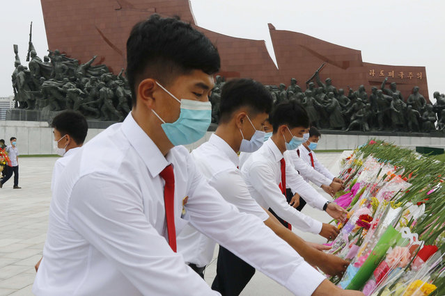 Pyongyang citizens visit Mansu Hill to pay homage to the bronze statues of President Kim Il Sung and Chairman Kim Jong Il ahead of the 27th anniversary of the death of President Kim Il Sung, in Pyongyang, North Korea, on Wednesday, July 7, 2021. (Photo by Cha Song Ho/AP Photo)