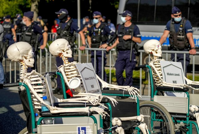 Medical stuff push skeletons in wheel chairs protesting in front of the Chancellery in Warsaw, Poland, Saturday, September 11, 2021. (Photo by Czarek Sokolowski/AP Photo)