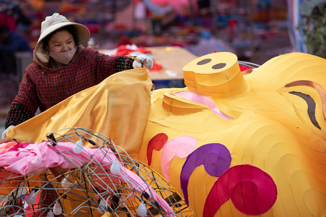 A woman works on a pig-shaped giant lantern at a plaza in Huangshan, Anhui, China on February 1, 2019. (Photo by Reuters/China Stringer Network)