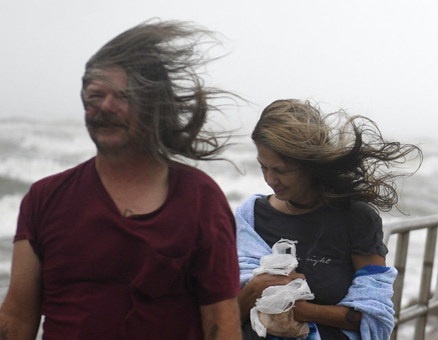 People shield their faces from wind and sand ahead of Tropical Storm Nicholas, Monday, September 13, 2021, on the North Packery Channel Jetty in Corpus Christi, Texas. Lifeguards paroled the beach to warn people of the upcoming conditions. (Photo by Annie Rice/Corpus Christi Caller-Times via AP Photo)