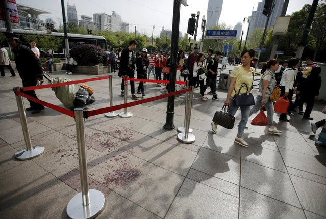 People walk by an area where two people were injured in a knife-wielding attack near People's Square in central Shanghai April 17, 2015. (Photo by Carlos Barria/Reuters)