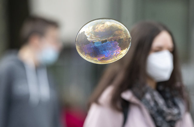 A soap bubble flies in front of people with mouth and nose protection in Stuttgart, Germany, Friday, October 9, 2020. Chancellor Merkel is discussing the situation with the mayors of the eleven largest German cities in view of the sharp rise in corona figures. (Photo by Sebastian Gollnow/dpa via AP Photo)