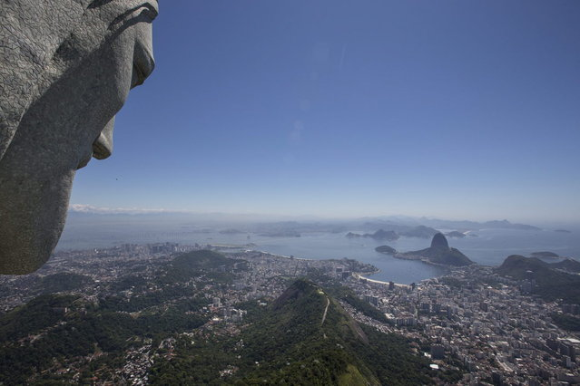 The Christ Redeemer statue, left, overlooks Guanabara bay in Rio de Janeiro, Brazil, Tuesday, January 21, 2014. The famed statue is being examined after two fingers and the head were chipped during recent lightning storms. Officials say they'll place more lightning rods on the statue in an effort to prevent future damage. (Photo by Felipe Dana/AP Photo)