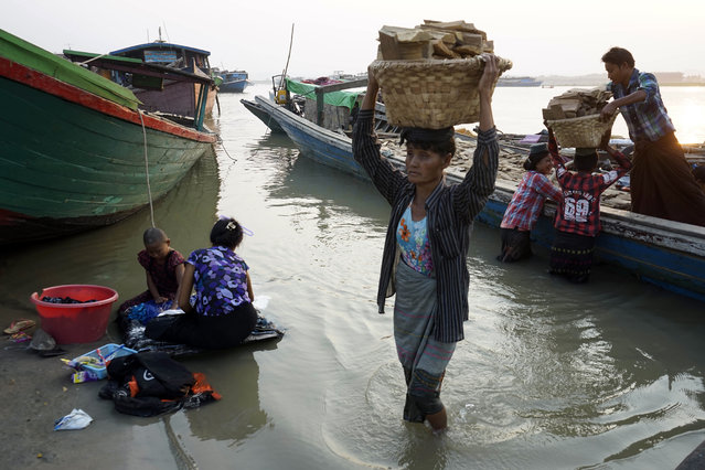 Myanmar women unload logs from a boat on the bank of Ayeyarwaddy River, on International Women's Day in Mandalay, Myanmar, Tuesday, March 8, 2016. Migrant workers living along Ayeyarwaddy riverbank earn bout 5000 Kyats (US Dollar 4) a day for loading and unloading goods. (Photo by Hkun Lat/AP Photo)