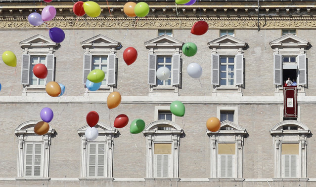 Colored balloons float as Pope Francis delivers his blessing during the Angelus prayer from his studio overlooking St. Peter's Square at the Vatican, Sunday, January 29, 2017. (Photo by Alessandra Tarantino/AP Photo)