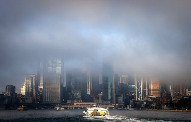 Fog covers buildings in the city as a ferry heads towards Circular Quay on June 11, 2021 in Sydney, Australia. Fog caused delays to ferry services and for drivers into the city due to reduced visibility. (Photo by David Gray/Getty Images)