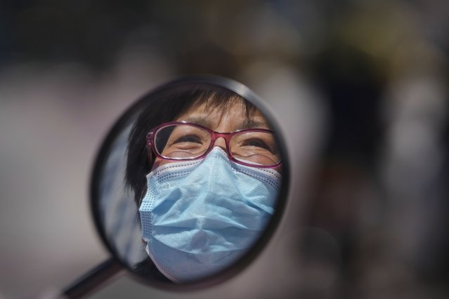 A woman wearing a face mask to help curb the spread of the coronavirus is reflected in her wing mirror of her electric-powered scooter as she waits at an intersection in Beijing, Tuesday, October 12, 2021. (Photo by Andy Wong/AP Photo)