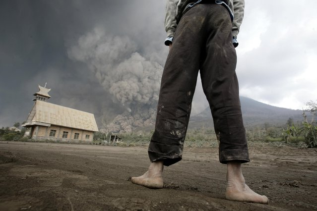 A man looks on as Mount Sinabung erupts near Bekerah village, in Karo district, North Sumatra, on February 1, 2014. Three men were burned and taken to hospital after being engulfed in heat clouds of Mount Sinabung in Indonesia, local officials said. (Photo by Chaideer Mahyuddin/AFP Photo)