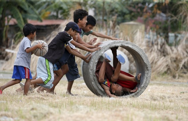 Boys play with a drainage culvert used for flood control in Las Pinas, Metro Manila February 28, 2016. (Photo by Erik De Castro/Reuters)