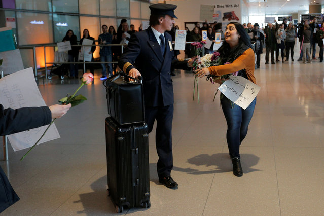 An opponent of U.S. President Donald Trump's executive order travel ban hands a flower to a member of a Lufthansa flight crew at Logan Airport in Boston, Massachusetts, U.S. February 3, 2017.  The Lufthansa flight carried several Boston area college students who had previously been denied travel under the travel ban. (Photo by Brian Snyder/Reuters)