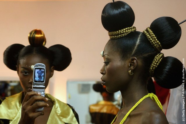 Nigerian fashion models Mary Jane Unueroh and Fome Emede (L) take a photo themselves with a cell phone behind the curtain  during their fashion show  to promote ethnic fashion June 13 in Tel Aviv, Israel