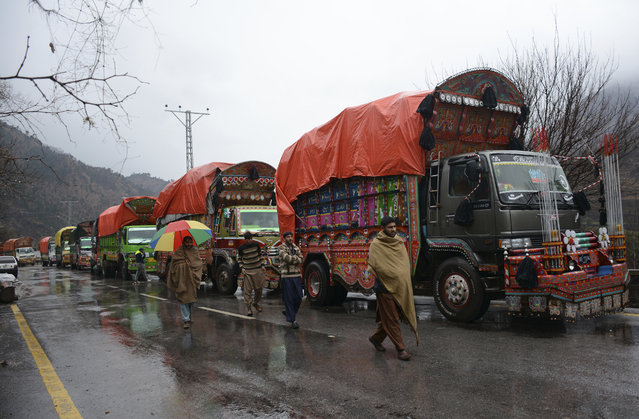 """Pakistani Kashmiris walk past India-bound cargo trucks, parked as road is closed to Indian Kashmir, in the border town of Chakoti at Line of Control in Pakistani Kashmir, Tuesday, February 26, 2019. Pakistan said India launched an airstrike on its territory early Tuesday that caused no casualties, while India said it targeted a terrorist training camp in a pre-emptive strike that killed a """"very large number"""" of militants. (Photo by Abdul Razaq/AP Photo)"""