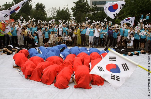South Koreans wave national flags during the 66th Independence Day ceremony in Seoul, South Korea