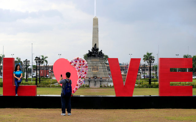 """People take pictures of a """"LOVE"""" display day before Valentine's Day in Rizal park, metro Manila, Philippines February 13, 2017. (Photo by Romeo Ranoco/Reuters)"""