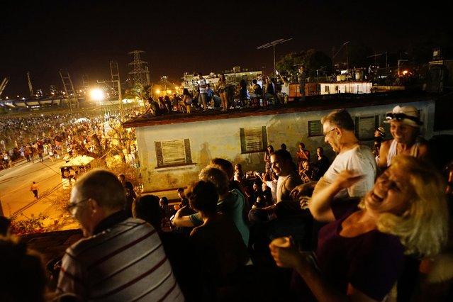 People watch the Rolling Stones concert on the terraces of the houses near the venue in Havana, Cuba, Friday March 25, 2016. (Photo by Ramon Espinosa/AP Photo)