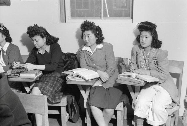 Three young women seated in a biology classroom, Kiyo Yoshida, Lillian Wakatsuki, Yoshiko Yamasaki, at the Manzanar War Relocation Center in California, in this 1943 handout photo. (Photo by Courtesy Ansel Adams/Library of Congress, Prints and Photographs Division/Reuters)