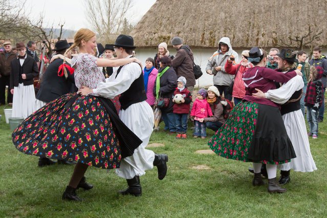 """Local residents take part in the annual Easter festival of """"watering the girls"""" at the ethnographic museum in Szenna, Hungary on March 29, 2016. (Photo by Xinhua/Barcroft Media)"""