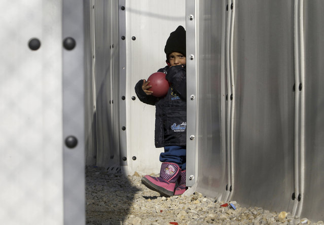 A refugee child holds a ball while walking between tents at the transit center for refugees near northern Macedonian village of Tabanovce on the border with Serbia, Monday, March 28, 2016. (Photo by Boris Grdanoski/AP Photo)