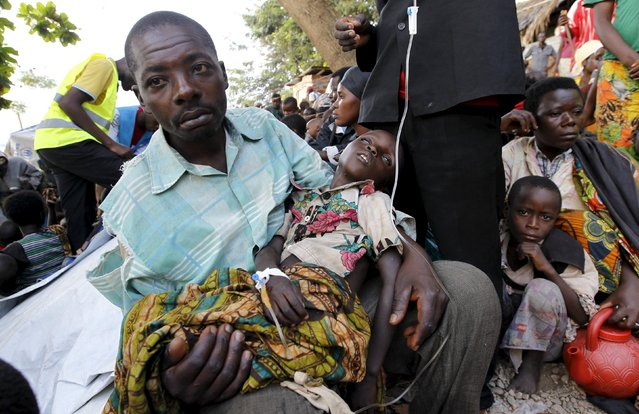 A Burundian refugee carries his sick child as he receives treatment at a makeshift clinic on the shores of Lake Tanganyika in Kagunga village in Kigoma region in western Tanzania, as they wait for MV Liemba to transport them to Kigoma township, May 17, 2015. (Photo by Thomas Mukoya/Reuters)