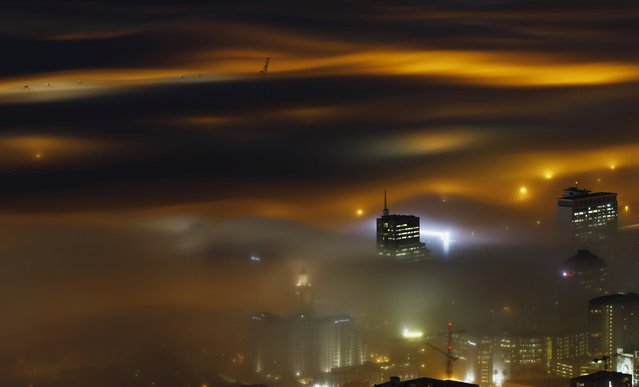 A long exposure picture shows a seasonal fog illuminated by the lights of Cape Town harbour as the city prepares for the start of the southern hemisphere winter, in South Africa, in this May 8, 2012 file photo. (Photo by Mike Hutchings/Reuters)