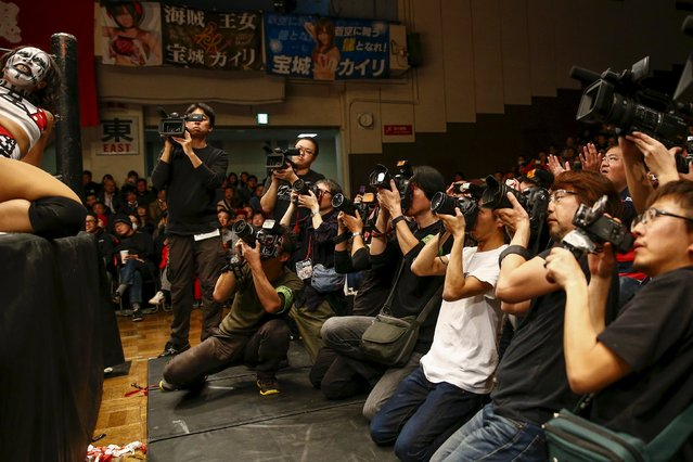 Members of the media take pictures of Holidead during a Stardom female professional wrestling show at Korakuen Hall in Tokyo, Japan, December 23, 2015. Professional women's wrestling in Japan means body slams, sweat, and garish costumes. But Japanese rules on hierarchy also come into play, with a culture of deference to veteran fighters. The brutal reality of the ring is masked by a strong fantasy element that feeds its popularity with fans, most of them men. (Photo by Thomas Peter/Reuters)