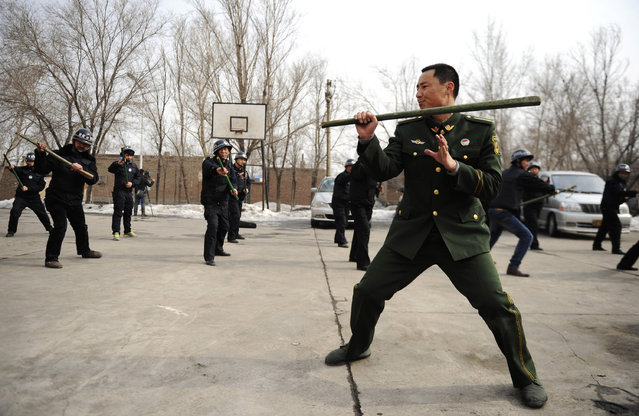 A paramilitary policeman demonstrates for officers during a security drill in Urumqi, Xinjiang autonomous region, March 18, 2014. Around 40 ethnic Han, Uighur and Kazak local officers attended the drill on Wednesday. (Photo by Reuters/Stringer)