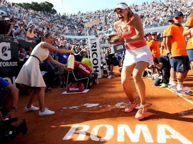 Maria Sharapova, of Russia, is sprayed with champagne as she holds the trophy after defeating Carla Suarez Navarro of Spain, at the end of the final match of the Italian Open tennis tournament, in Rome, Sunday, May 17, 2015. Sharapova won 4-6, 7-5, 6-1. (Photo by Ettore Ferrari/ANSA via AP Photo)