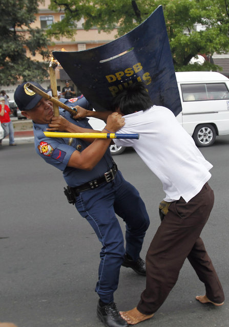 An anti-riot policeman grabs a protester during a rally in front of the U.S. Embassy in Manila March 27, 2014. The protesters denounced the Agreement on Enhanced Defense Cooperation that could legalize U.S. military presence in the Philippines and also protested against the upcoming visit of U.S. President Barack Obama in April, local media reported. (Photo by Romeo Ranoco/Reuters)
