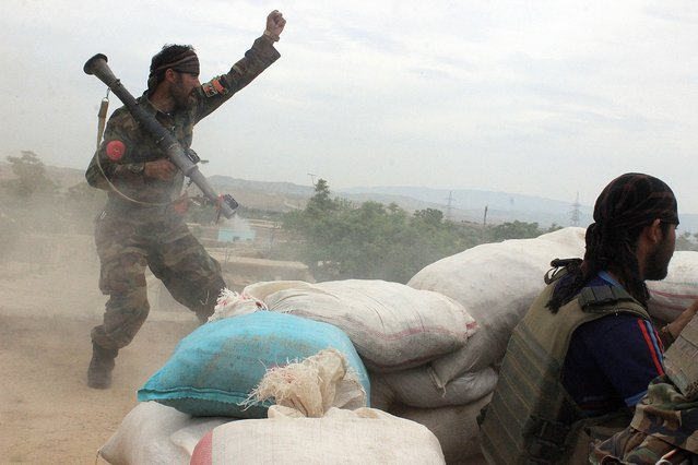 An Afghan National Army soldier, left, shouts against the Taliban, after firing a rocket towards Taliban positions, on the outskirts of Kunduz, northern Afghanistan, Saturday, April 16, 2016. Officials say Afghan forces have repelled a Taliban assault on the northern city of Kunduz, which the insurgents had briefly seized last year. (Photo by Najim Rahim/AP Photo)