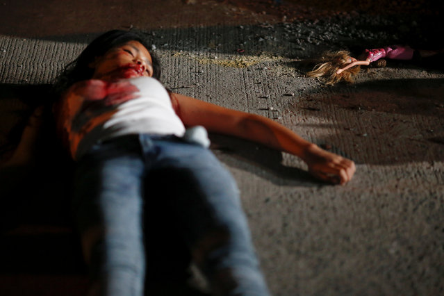 "A 17 year old girl lays dead next to her doll after she and her friend were killed by unknown motorcycle-riding gunmen, in an alley in Manila, Philippines early October 26, 2016. According to the police, a sign on a cardboard reading ""Tulak ka, hayop ka"", which translates to ""You are a (drug) pusher, you are an animal"" was found with the body of girl's friend. (Photo by Damir Sagolj/Reuters)"