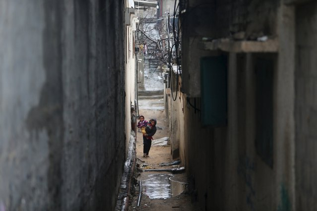 A Palestinian boy holds his sister as he walks in an alley at Khan Younis refugee camp on a rainy day in the southern Gaza Strip February 22, 2016. (Photo by Ibraheem Abu Mustafa/Reuters)