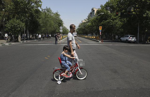 In this Friday, May 17, 2019 photo, a man with his daughter cross Enqelab-e-Eslami (Islamic Revolution) street in downtown Tehran, Iran. (Photo by Vahid Salemi/AP Photo)