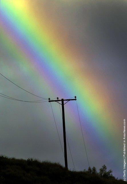 A rainbow appears in a stormy sky over a power line near San Fernando