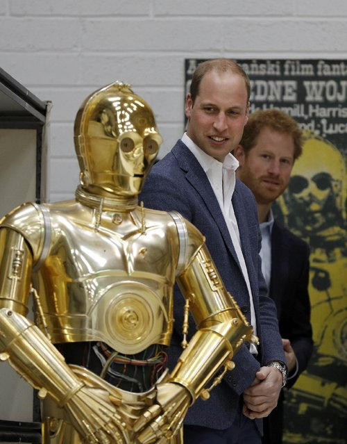 Britain Prince William and Prince Harry look at droid C3P0 from Star Wars as they visit the creature and droid department at Pinewood studios in Iver Heath, west of London, Britain on April 19, 2016. (Photo by Adrian Dennis/Reuters)