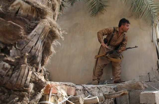 A Kurdish gunman looks at Shi'ite militiamen positions during clashes in Tuz Khurmato, Iraq, April 24, 2016. (Photo by Goran Tomasevic/Reuters)