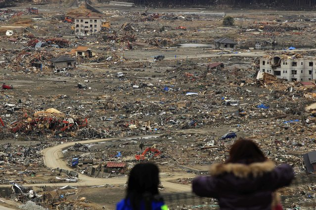 In the March 21, 2011, file photo, people look out at tsunami damage from a hill where there is a shelter set up in a school in Minamisanriku, Japan. (Photo by Matt Dunham/AP Photo)