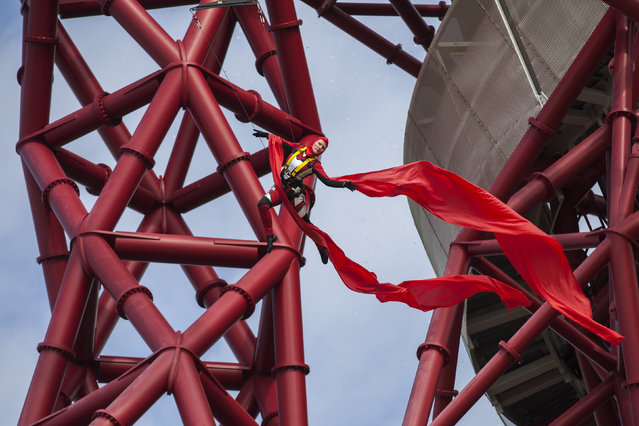 An acrobat abseils from the 114.5 metre high ArcelorMittal Orbit tower at the Olympic Park on April 5, 2014 in London, England. The Queen Elizabeth Olympic Park in east London has opened to the public for the first time since the London 2012 Games. It is the biggest park to be opened in London for a century and it is hoped that the attraction will revitalise the neighbourhood and attract tourists. (Photo by Rob Stothard/Getty Images)