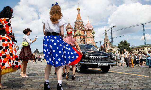Women by a vintage car during the 2019 GUM Motor Rally featuring classic cars in Moscow, Russia on July 28, 2019. (Photo by Artyom Geodakyan/TASS via Getty Images)