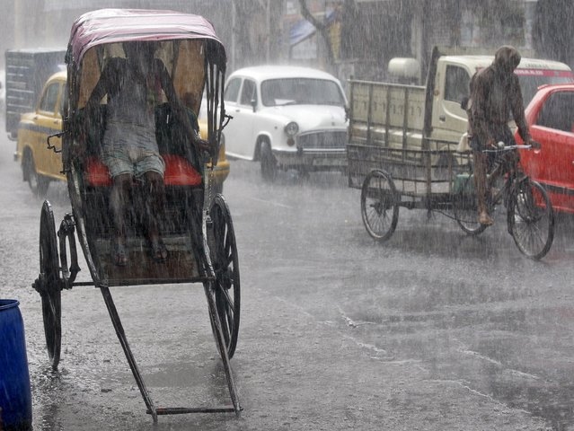 A man takes shelter inside his rickshaw during a heavy rain shower in Kolkata, India, June 25, 2015. (Photo by Rupak De Chowdhuri/Reuters)