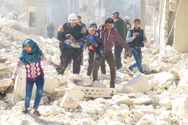 People and a civil defence personnel carry children at a damaged site after an air strike on rebel-held Idlib city, Syria March 19, 2017. (Photo by Ammar Abdullah/Reuters)