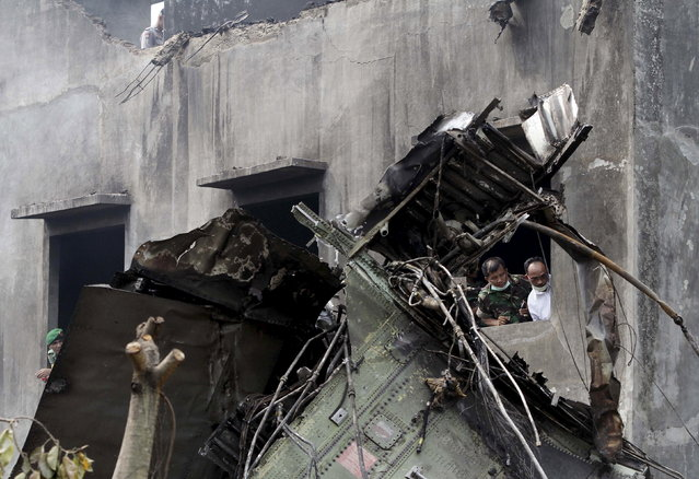 Security forces examine the wreckage of an Indonesian military C-130 Hercules transport plane after it crashed into a residential area in the North Sumatra city of Medan, Indonesia, June 30, 2015. (Photo by Roni Bintang/Reuters)