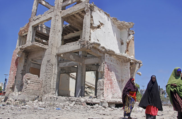 Somali women walk past a destroyed building after a suicide car bomb attack in the capital Mogadishu, Somalia Wednesday, May 22, 2019. A police spokesman said the attack killed at least six people and injured more than a dozen, while Islamic extremist group al-Shabab claimed responsibility for the blast, saying it targeted vehicles carrying government officials. (Photo by Farah Abdi Warsameh/AP Photo)