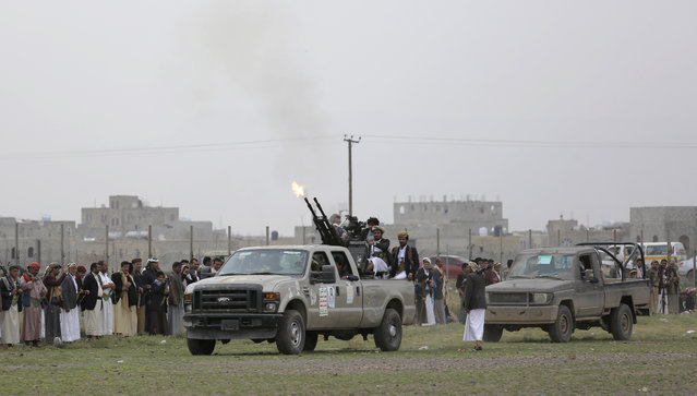 Houthi rebel fighters fire their weapons in the air as they take off to a battlefront following a gathering aimed at mobilizing more fighters for the Houthi movement, in Sanaa, Yemen, Thursday, August 1, 2019. The conflict in Yemen began with the 2014 takeover of Sanaa by the Houthis, who drove out the internationally recognized government. Months later, in March 2015, a Saudi-led coalition launched its air campaign to prevent the rebels from overrunning the country's south. (Photo by Hani Mohammed/AP Photo)