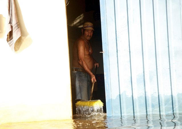 A man sweeps water of a house in a flooded zone in Guasdualito, in the state of Apure, Venezuela, July 4, 2015. (Photo by Carlos Eduardo Ramirez/Reuters)