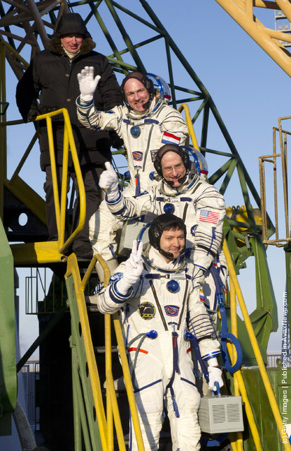 ESA Russian cosmonaut Oleg Kononenko, NASA astronaut Don Pettit and ESA astronaut Andre Kuipers wave goodbye to the crowd gathered at the foot of the Soyuz launch pad stairs before taking the elevator to the top of the Soyuz rocket