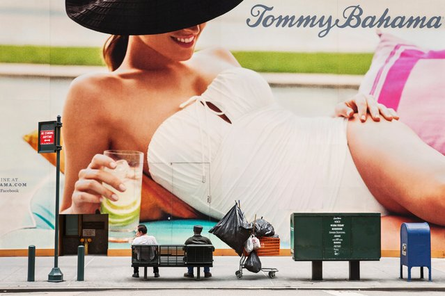 Dvir says these ads, always in the peripheral vision, turn the people moving through the space into passive spectators. Pictured here, two men sit on a bench next to a Tommy Bahama billboard on 5th Avenue in New York, June 13, 2012. (Photo by Natan Dvir/Polaris)